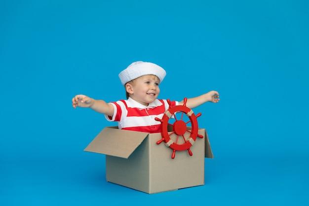 幸せな子供は青い壁に対して船長になることを夢見ています。