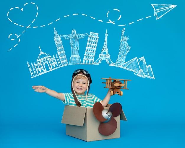 幸せな子供は青い紙の壁に対してパイロットになることを夢見ています。