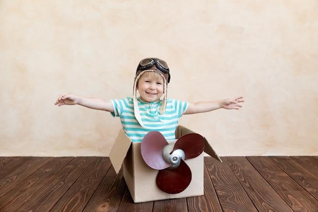 幸せな子供は段ボール箱で遊ぶパイロットになることを夢見ています。
