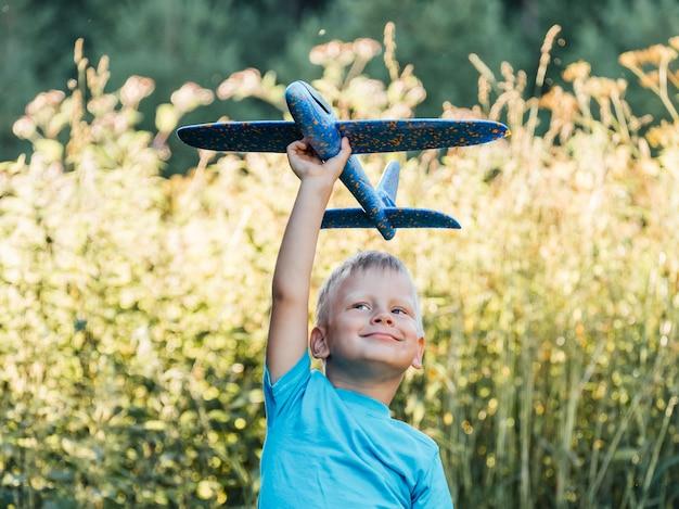 Счастливый ребенок мечтает путешествовать и играть с самолетом