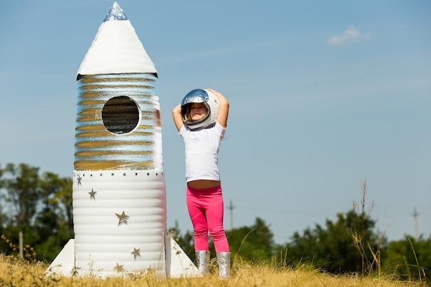 행복 한 아이 손으로 만든 로켓 재생 우주 비행사 의상을 입고.