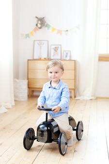 Happy child drives a toy vintage car in a children's room. funny child playing at home. active little boy driving a children's car in kindergarten. toddler driving a retro car, boy in a toy car