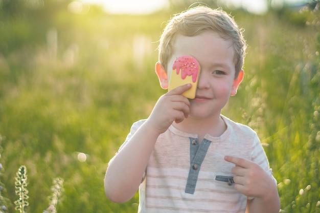 Счастливый ребенок ест печенье в виде мороженого
