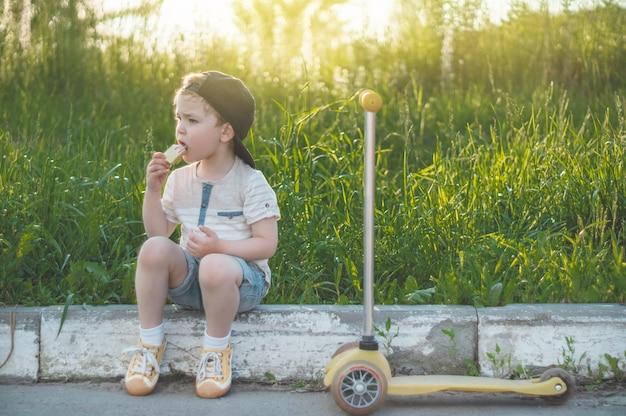 Счастливый ребенок ест печенье на открытом воздухе