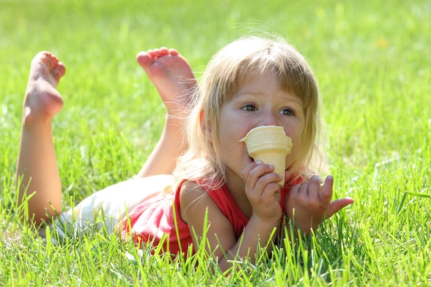 Счастливый ребенок ест мороженое на природе в парке