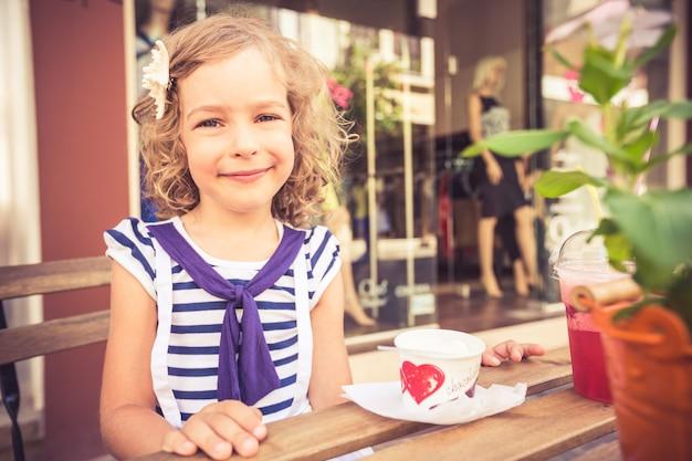 屋外の夏のカフェでアイスクリームを食べて幸せな子