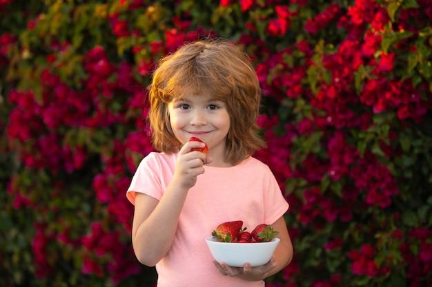 幸せな子供は夏の屋外でイチゴを食べる