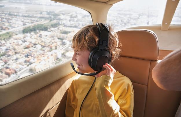 화창한 날 비행기 창에서 도시 전망을 즐기는 행복한 아이
