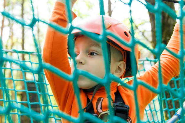 Happy child enjoying in a climbing adventure park