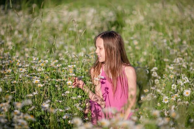 Happy child in field beautiful girl in dress in a straw hat