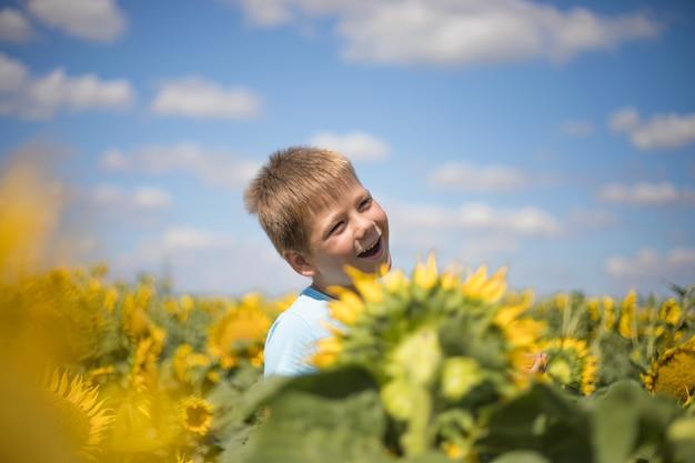幸せな子フィールド屋外のヒマワリの自由と幸福の概念。青い空を背景に緑の春のフィールドで楽しんでいる子供。健康的でアクティブなライフスタイルのコンセプト