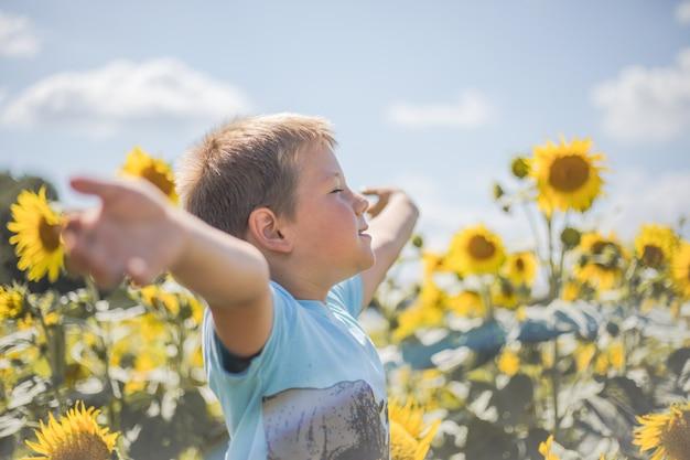 ハッピーチャイルドフィールド緑の春で楽しんでいるヒマワリ屋外キッドの自由と幸福の概念