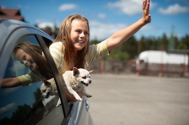 열린 차창 밖을 바라보는 행복한 아이 소녀와 개 치와와