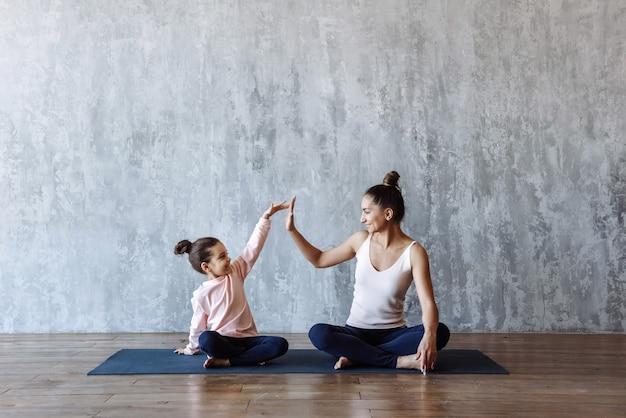 행복한 아이 소녀와 어머니는 체육관에 앉아 요가를 연습하면서 함께 스포츠를 하러 간다 프리미엄 사진