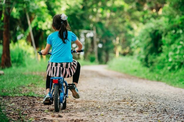 夕日の光運動で夜の村の公園でサイクリング幸せな子供女の子。