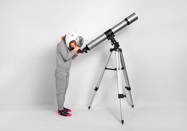 Счастливый ребенок девочка, одетая в костюм космонавта смотрит в большой телескоп.