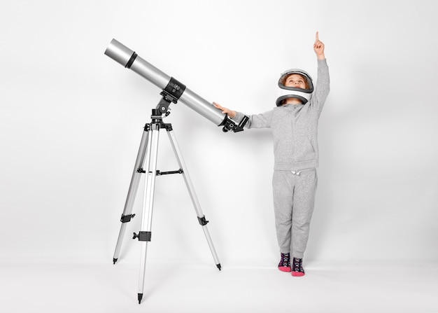 Счастливый ребенок девочка, одетая в костюм космонавта, стоя рядом с телескопом.