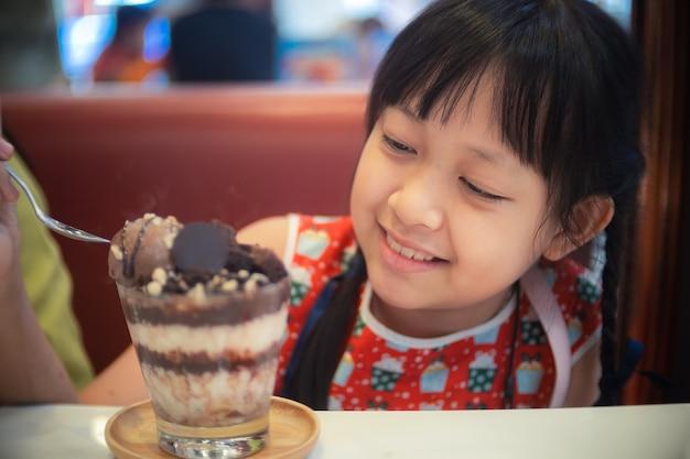 미소로 초콜릿 아이스크림을 먹는 행복 한 아이 소녀