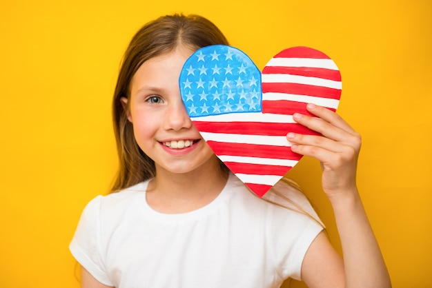 Happy child girl holds american flag on yellow background. patriotism, independence day, flag day concept. memorial day