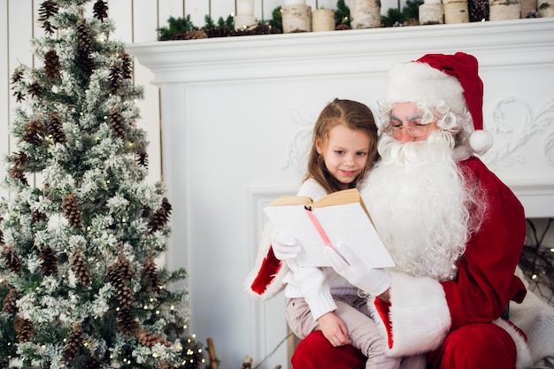 彼が本を読んでいる間サンタを抱き締める幸せな子供の女の子