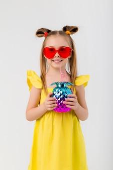 Счастливая девушка ребенка в солнечных очках держа стекло с изолятом коктеиля