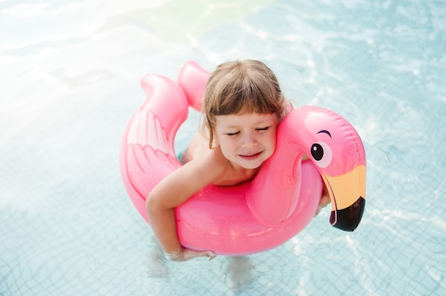 Happy child girl is swimming with rubber ring flamingo in swimming pool.