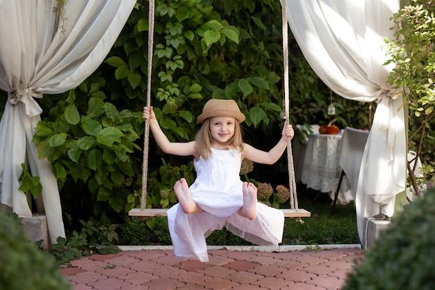Счастливый ребенок девочка смеется и качается на качелях летом