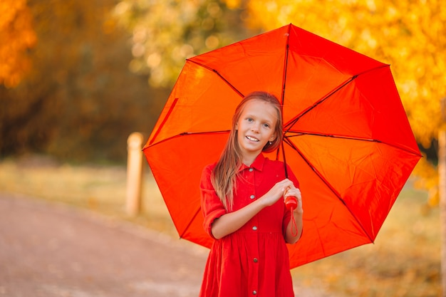 Happy child girl laughs under red umbrella