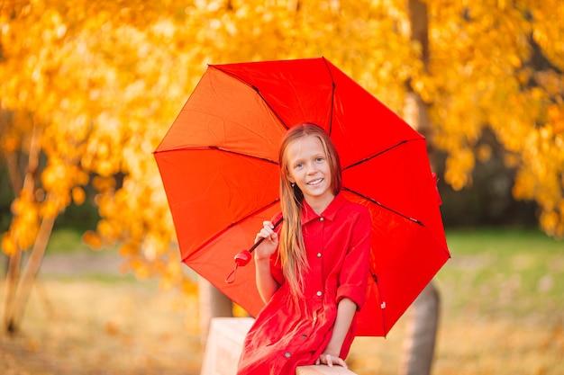 赤い傘の下で笑う幸せな子供の女の子