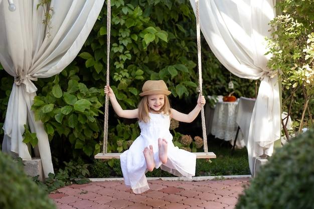 Счастливая девушка ребенка на качелях летом