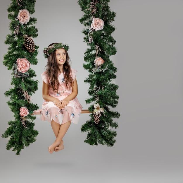 スタジオでクリスマスの装飾とブランコで幸せな子の女の子