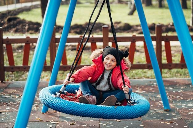 Счастливая детская девочка на качелях
