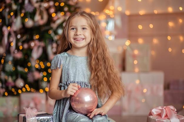 新年のライトとクリスマスツリーの背景に幸せな子供の女の子