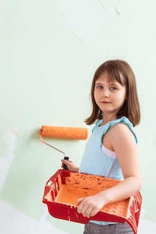Счастливый ребенок девочка красит стену оранжевой краской