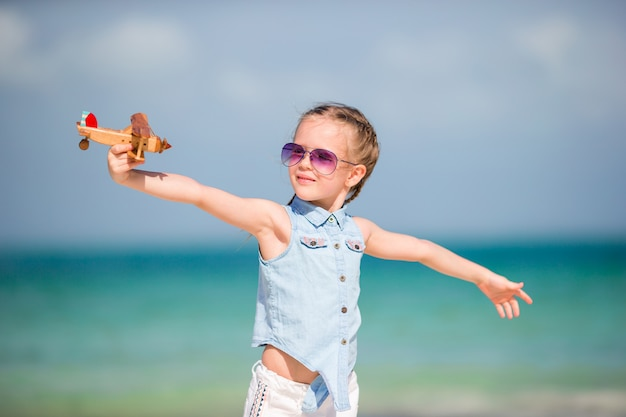 Happy child girl playing with toy airplane on the beach. kid dream of becoming a pilot