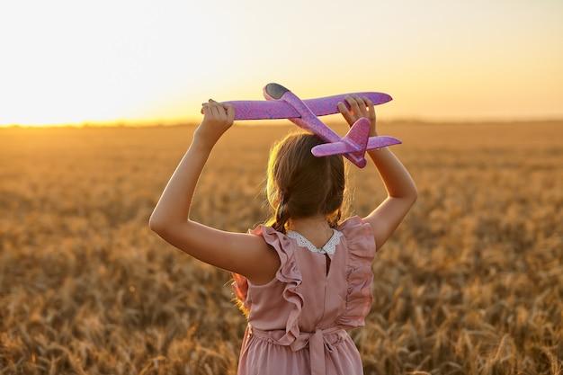 행복한 아이, 여름 밀밭에서 장난감 비행기를 가지고 노는 소녀. 작은 딸은 비행을 꿈꿉니다. 야외에서 노는 평온한 아이