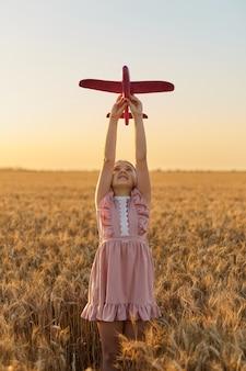 행복한 아이, 여름 밀밭에서 장난감 비행기를 가지고 노는 소녀