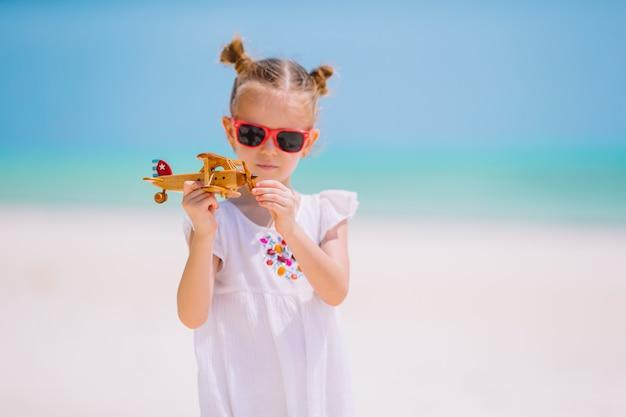 Счастливая девушка ребенка играя с самолетом игрушки на пляже. детская мечта стать летчиком
