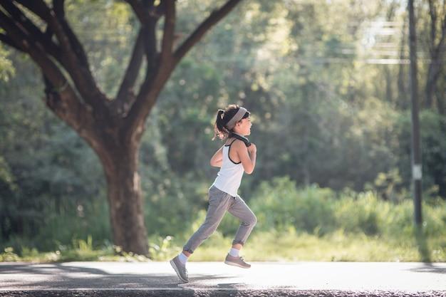 Счастливая девочка ребенка работает в парке летом в природе. теплый солнечный свет.