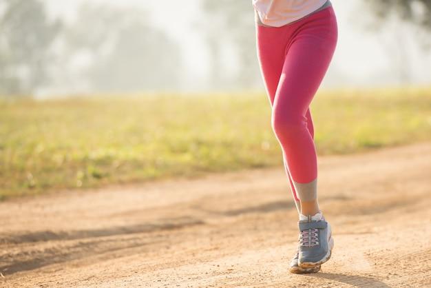自然の中で夏の草原を走る幸せな子供の女の子。暖かい日差しのフレア。アジアのリトルが公園で走っている。子供の発達のためのアウトドアスポーツとフィットネス、運動と競技学習。