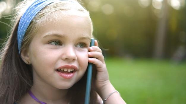 夏の公園で携帯電話で話している幸せな子の女の子。