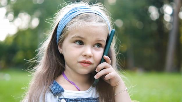 여름 공원에서 휴대 전화에 얘기 하는 행복 한 아이 소녀.