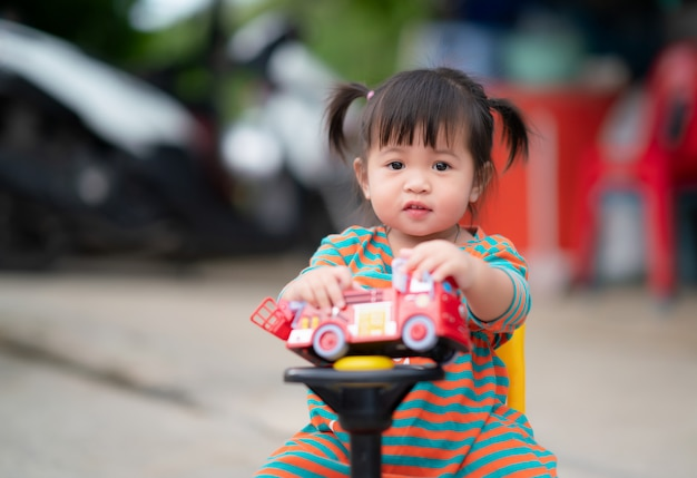 Happy child girl with a car toy, cute kid playing outdoors.