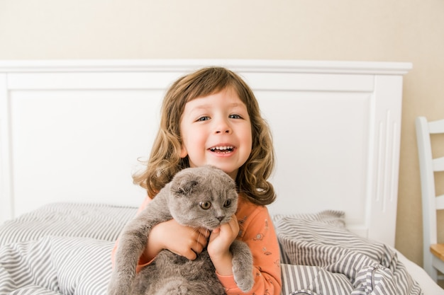 Happy child girl with cat in bed little girl smilling and having fun with scottish fold cat