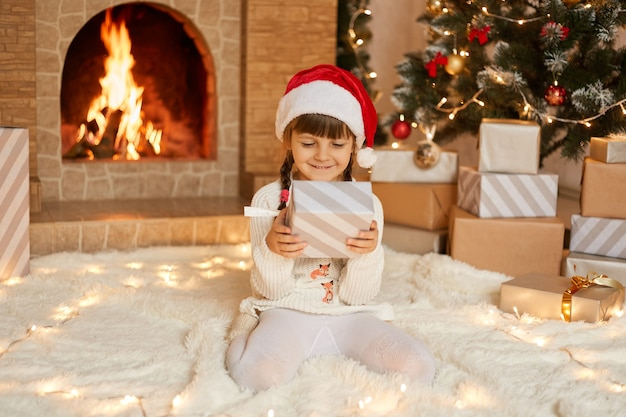 Happy child girl with christmas present at home sitting on warm carpet