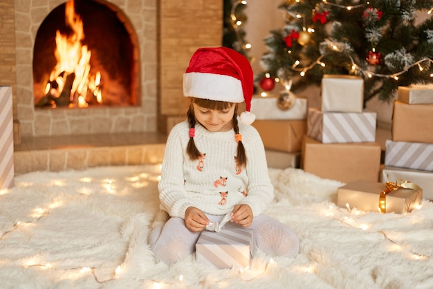 Happy child girl with christmas present sitting on floor near xmas tree, looking at gift box with ribbon in her hands, wearing white jumper and red xmas hat, poses near fireplace.