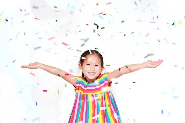 흰색 배경에 색종이 함께 행복 한 아이 소녀. 새해 복 많이 받으세요 또는 축하 개념.