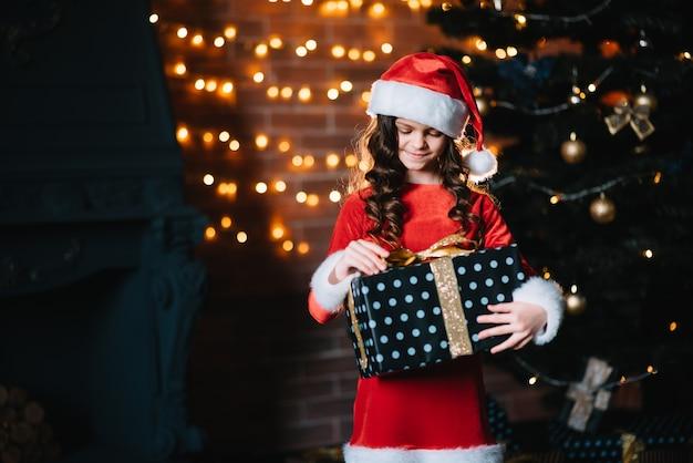 ギフトボックスと幸せな子の女の子。休日、プレゼント、クリスマスのコンセプト。