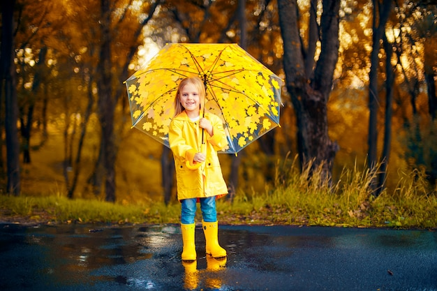 Happy child girl with an umbrella and rubber boots an autumn walk