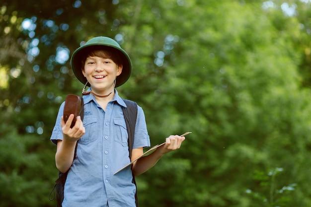 Счастливый ребенок отправляется в поход с рюкзаком в летней природе